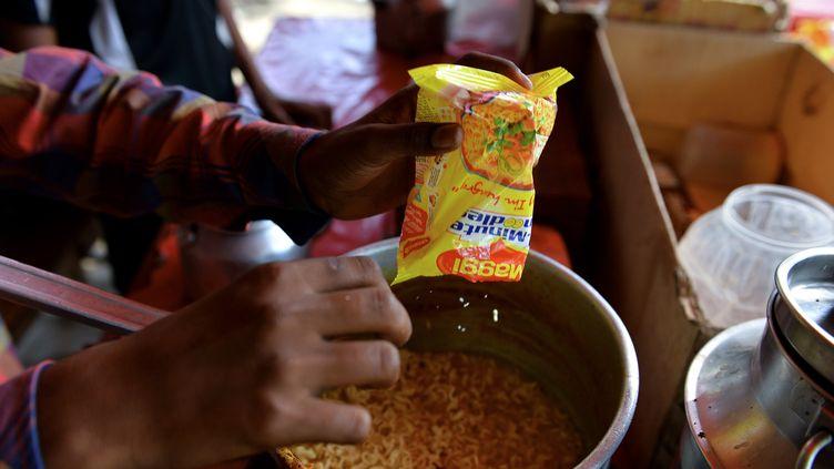 Un jeune Indien prépare des nouilles instantanées Maggi fabriquées par Nestlé, le 3 juin 2015 à New Delhi. (CHANDAN KHANNA / AFP)