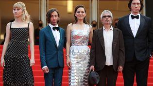 """""""Annette"""" est le film d'ouverture de ce 74e festival de Cannes. L'équipe monte les marches avant la première projection cannoise de 2021. De gauche à droite, la chanteuse belge Angèle, l'acteur américain Simon Helberg, Marion Cotillard, le réalisateur du film Leos Carax et Adam Driver. (VALERY HACHE / AFP)"""