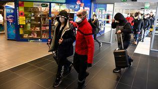 Des voyageurs en provenance de Milan, en Italie, sont évacués après avoir été temporairement confinés dans un bus à la gare routière de Lyon-Perrache, lundi 24 février 2020. (JEAN-PHILIPPE KSIAZEK / AFP)