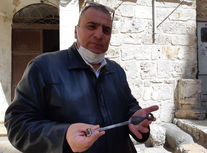 Le gardien du Saint-Sépulcre a fermé l'église. Adeeb Jawad Joudeh Al Husseini, gardien de l'église du Saint-Sépulcre, masque sanitaire sur le menton, montre la clef du lieu de culte. (FRÉDÉRIC MÉTÉZEAU / RADIO FRANCE)