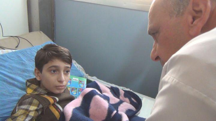 Le docteur Hadid réconforte le jeune Abdel grièvement blessé à la jambe gauche par un obus à Alep, en Syrie. (GILLES GALLINARO / RADIO FRANCE)