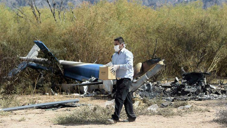 Un homme récupère des indices sur les lieux du crash de l'hélicoptère ayant coûté la vie à dix personnes dont Camille Muffat, Florence Arthaud et Alexis Vastine.