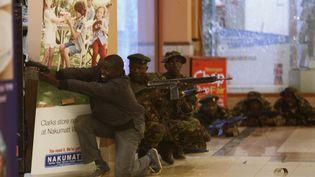 Des soldats et un policierkényan armé à la recherche des hommes armés et masqués qui ont ouvert le feu le 21 septembre 2013 sur les clients et le personnel d'un centre commercial de luxe à Nairobi (Kenya). (GORAN TOMASEVIC / REUTERS)