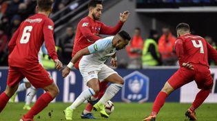 Le milieu de terrain de l'OM Dimitri Payet cerné par les joueurs d'Andrezieux lors des 32e de finale de la Coupe de France à Saint-Etienne (Loire), le 6 janvier 2019. (JEFF PACHOUD / AFP)