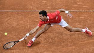 Novak Djokovic est accroché par Lorenzo Sonego. (FILIPPO MONTEFORTE / AFP)