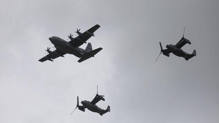 Un avion américain Lockheed C-130 Hercules et des Boeing-Bell V-22 Osprey survolent Carentan, en Normandie,le 5 juin 2019, dans le cadre des commémorations du Débarquement. (LUDOVIC MARIN / AFP)