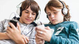 Des adolescents écoutent de la musique sur leur smartphones. (VOISIN / PHANIE / AFP)