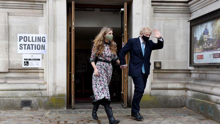 Le Premier ministre britannique Boris Johnson et sa fiancée Carrie Symonds, le 6 mai 2021 à la sortie d'un bureau de vote à Londres (Royaume-Uni) (KATE GREEN / ANADOLU AGENCY / AFP)