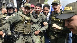 Des policiers colombiens accompagnent un officier vénézuelien, le 23 février 2019, àla frontière entre le Venezuela et la Colombie, àCucuta. (LUIS ROBAYO / AFP)