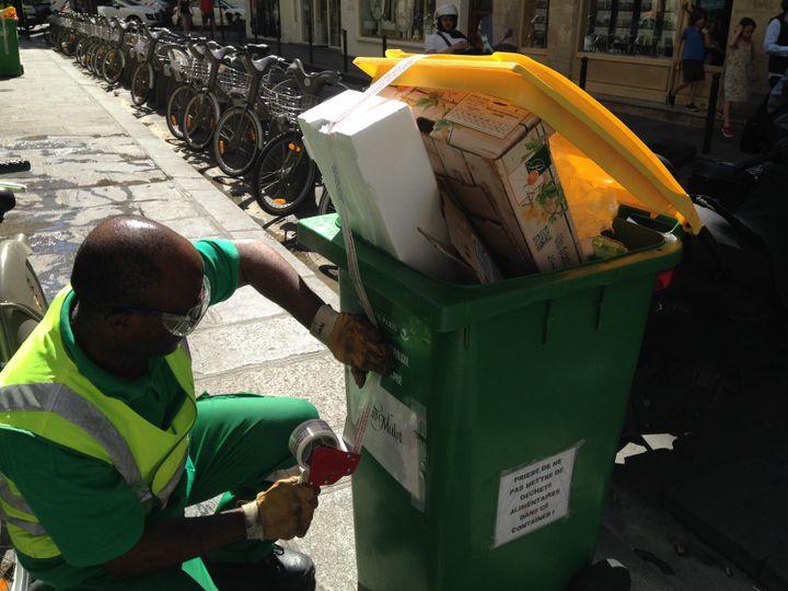 Jean-Marc condamne une poubelle jaune d'où dépassent du polystyrène, une barquette en bois et des sacs en plastique remplis de nourriture, le 30 juin 2015, dans le 6e arrondissement de Paris. (JULIE RASPLUS / FRANCETV INFO)
