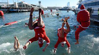 Pour eux, en revanche, Noël n'est pas une fête solennelle : ces trois nageurs en costume sautent dans le port de Barcelonepour une course de Noël à la nage qui réunissait plus de 300 participants peu frileux, ce 25 décembre. (JOSEP LAGO / AFP)