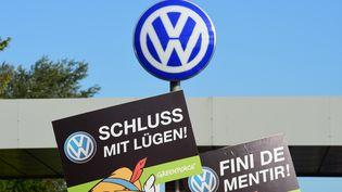 """Des activistes tiennent des pancartes """"Arrêtez de mentir"""" pour protester contre le scandale Volkswagen, le 25 septembre 2015 à Wolfsburg, en Allemagne. (JOHN MACDOUGALL / AFP)"""