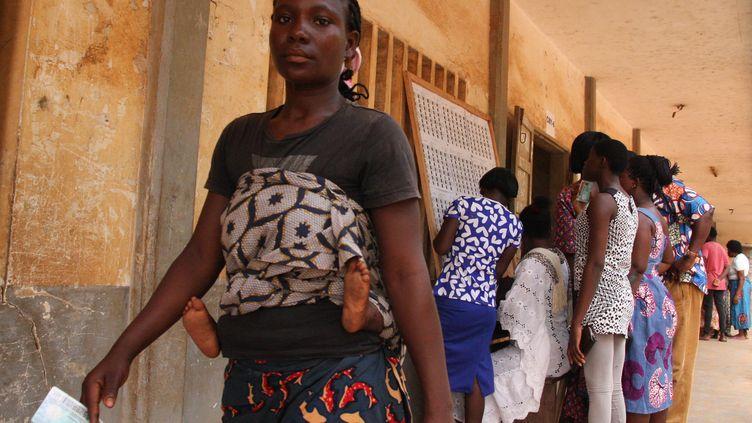 Des électeurs consultent une liste électorale dans un bureau de vote à Lomé, lors des législatives le 20 décembre 2018. (MATTEO FRASCHINI KOFFI / AFP)