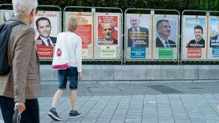 Deux électeurs passent devant lesaffiches de campagne des candidats à l'élection présidentielle, à Pau (Pyrénées-Atlantiques) le 10 avril 2017. (LAURENT FERRIERE / HANS LUCAS / AFP)