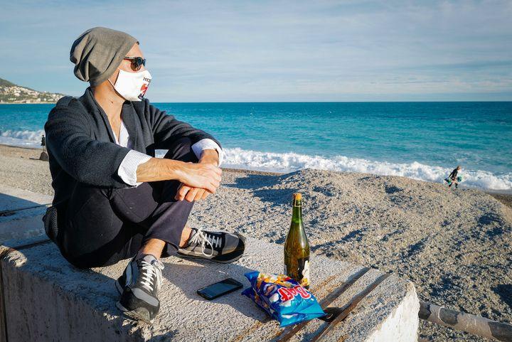 Un homme profite de la plage, à Nice (Alpes-Maritimes), peu avant 18 heures et le début du confinement mis en place pour le week-end, le 12 mars 2021. (ARIE BOTBOL / HANS LUCAS / HANS LUCAS VIA AFP)