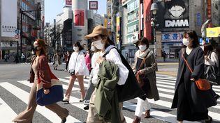 Des personnes portent un masque dans le quartier de Shibuya à Tokyo, le 22 février 2021. (RYOHEI MORIYA / YOMIURI / AFP)