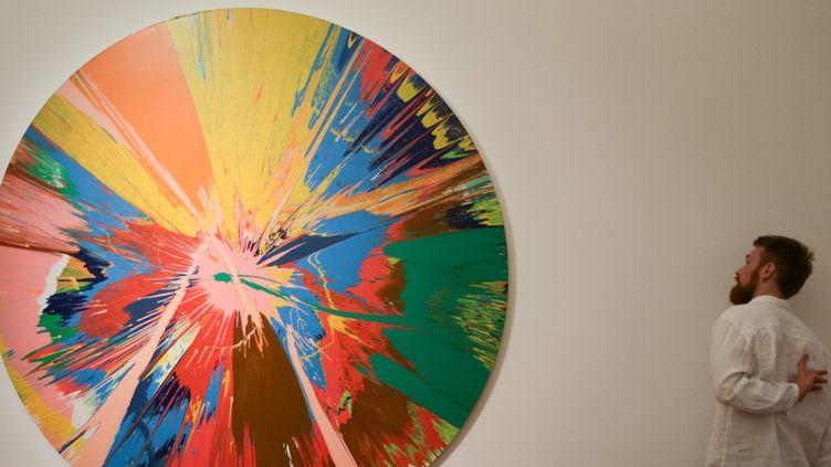 Un visiteur regarde la toile de Damien Hirts ''Beautiful, shattering, slashing, violent, pinky, hacking, sphincter painting' achetée par David Bowie  (DANIEL LEAL-OLIVAS / AFP)