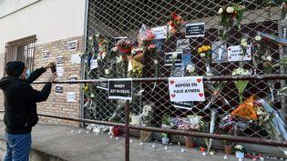 Une personne rend hommage à l'adolescent de 15 ans tué par balles à Bondy (Seine-Saint-Denis), devant l'Espace Nelson-Mandela, où les tirs ont eu lieu, le 28 février 2021. (BERTRAND GUAY / AFP)
