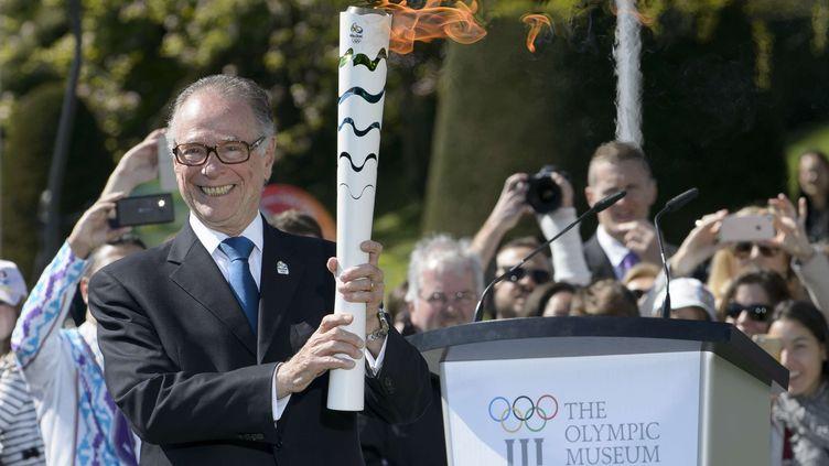 Le président du comité olympique brésilien, Carlos Arthur Nuzman, tout sourire, avec la flamme olympique dans les mains (ANTHONY ANEX/AP/SIPA / AP)