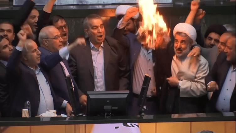 Des députés iraniens brûlent un drapeau américain, le 9 mai 2018 à Téhéran (Iran). (AP / YOUTUBE.COM)