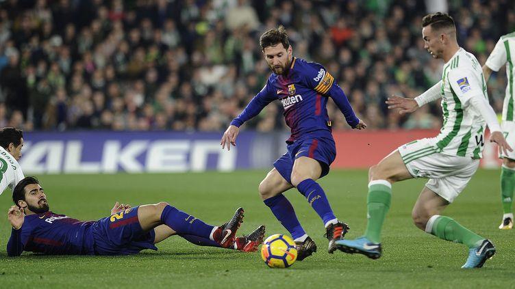 Lionel Messi au contact de la défense du Betis (CRISTINA QUICLER / AFP)