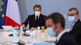 Emmanuel Macron assiste à un conseil de défense avec le ministre de la Santé, Olivier Veran, et le secrétaire général de l'Elysée, Alexis Kohler (au second plan), à Paris, le 12 novembre 2020. (THIBAULT CAMUS / AFP)