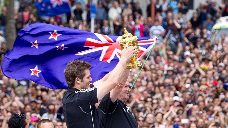 Le capitaine des All Blacks Richie McCaw et l'entraîneur néo-zélandais Graham Henry brandissent la Coupe Web Ellis, le 24 octobre 2011, à Auckland. (MARTY MELVILLE / AFP)