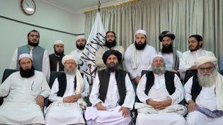 Lecofondateur du mouvement des talibans,Abdul Ghani Baradar (assis au centre, coiffé d'un turban noir), adresse dans une vidéo un message de félicitations à ses troupes entrées dans Kaboul, le 15 août 2021. (EYEPRESS NEWS / AFP)