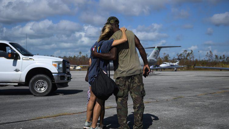 Unebénévoleaméricain avec un amià l'aéroport de Treasure Cay sur l'île d'Abaco aux Bahamas, le 11 septembre 2019, au lendemain de l'ouragan Dorian. (ANDREW CABALLERO-REYNOLDS / AFP)