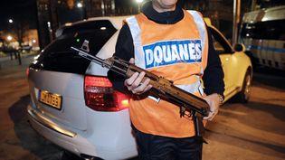 Un agent des douanes montre une kalachnikov trouvée dans le coffre d'un véhicule, le 22 novembre 2010, à Marseille (Bouches-du-Rhône). (ANNE-CHRISTINE POUJOULAT / AFP)