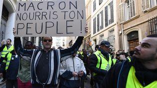 """A Marseille, ce manifestant brandit une pancarte """"Macron, nourris ton peuple"""". (BORIS HORVAT / AFP)"""