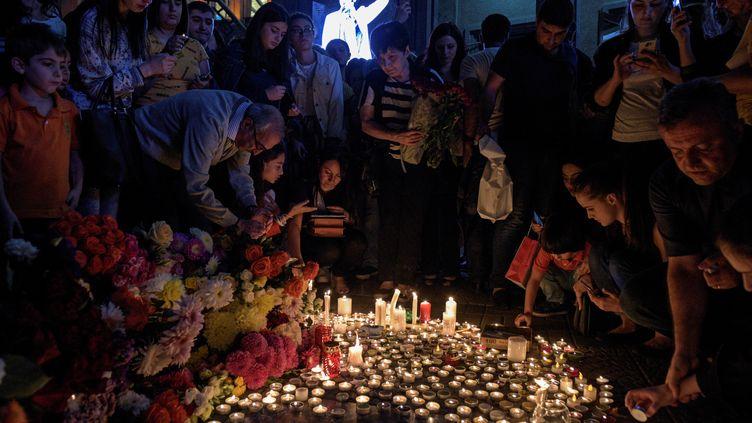 Des personnes viennent déposer fleurs et bougies en mémoire de Charles Aznavour, à Yerevan, en Arménie, le 1er octobre 2018. (KAREN MINASYAN / AFP)