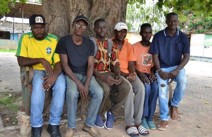 Karamo Keita (le troisème à droite) et ses amis expliquent les risques de l'émigration vers l'Europe. (Lamin KANTEH / AFP)