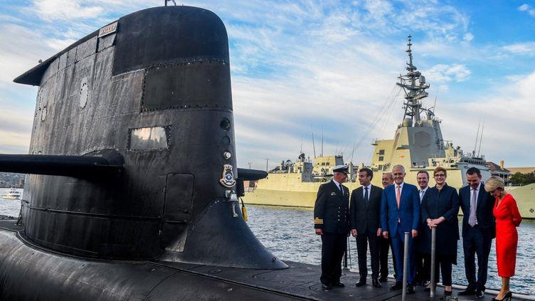 Le président de la République Emmanuel Macron et le ministre des Affaires étrangères Jean-Yves Le Drian aux côtés de l'ancienPremier ministre australien Malcolm Turnbull, sur un sous-marin à Sydney (Australie), le 2 mai 2018. (BRENDAN ESPOSITO / AFP)