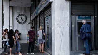 Devant un distributeur de billets, le 28 juin 2015 à Athènes. (ALEXANDROS MICHAILIDIS / AFP)
