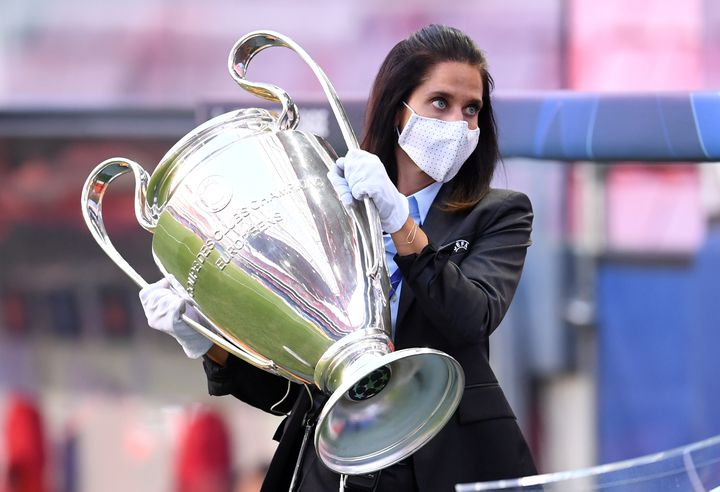 Une membre du staff de l'UEFA, masquée et gantée, porte la coupe aux grandes oreilles. (DAVID RAMOS / POOL)