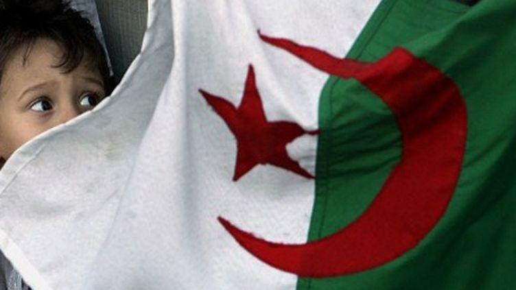 Un enfant regardant le drapeau algérien à Alger (AFP - Fayez NURELDINE )