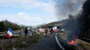 Des contre-manifestants occupent un barrage tenu la veille par des militants Kanak, le 9 décembre 2020 à Paita. Ils veulent securiser la circulation et manifester leur colère contre les blocages organisés par les opposants au projet de vente de l'usine du Sud. (THEO ROUBY / HANS LUCAS / AFP)