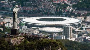 Le Christ du Corcovado, symbole de Rio et du Brésil, et en arrière-plan le mythique stade de Maracana, où se déroulera la finale de la Coupe du monde, le 13 juillet prochain. (YASUYOSHI CHIBA / AFP )