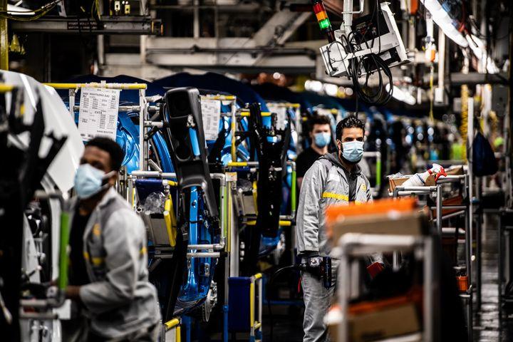 Des employés d'une usine Renault, à Flins-sur-Seine (Yvelines), travaillent avec un masque de protection, le 6 mai 2020. Les entreprises sont un des lieux où se sont déclarés le plus de clusters. (MARTIN BUREAU / AFP)