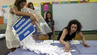 Dans un bureau de vote d'Athènes, des femmes procèdent au dépouillement après le vote des Grecs au référendum, dimanche 5 février 2015. ( MARKO DJURICA / REUTERS)