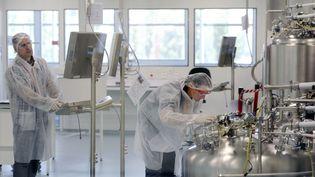Deux techniciens travaillent sur une ligne de production à l'usine Sanofi de Neuville-sur-Saône (Auvergne-Rhône-Alpes) (PHILIPPE DESMAZES / AFP)