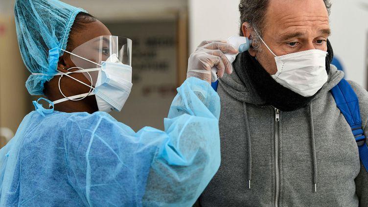 Une infirmière prend la température d'un patient dans un centre médical à Paris, le 1er avril 2020. (BERTRAND GUAY / AFP)