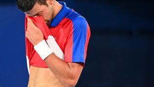 Novak Djokovic voit ses rêves d'or olympique s'envoler, le 30 juillet 2021 à Tokyo. (VINCENZO PINTO / AFP)