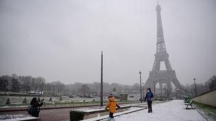 Des Parisiens jouent dans la neige non loin de la Tour Eiffel, le 16 janvier 2021. (MARTIN BUREAU / AFP)