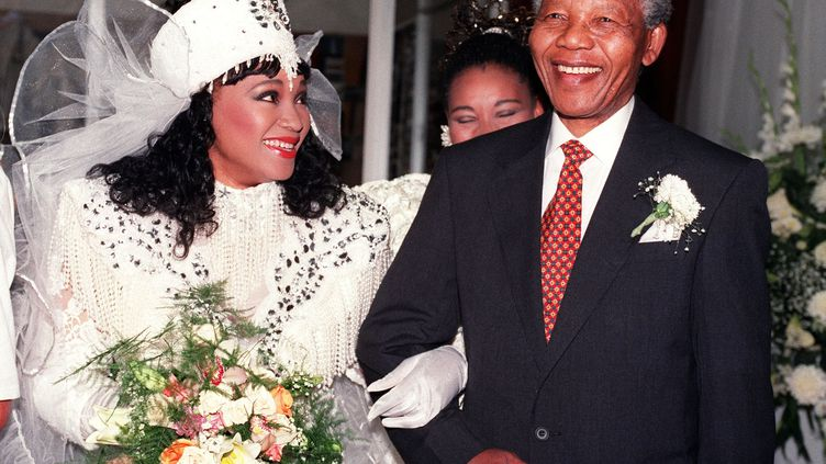 Zindzi Mandela souriante, au bras de son père Nelson Mandela, et en tenue traditionnelle xhosa pour son marriage avec l'homme d'affaires Zweli Hlongwane, le 26 octobre 1992 à Soweto, en Afrique du Sud.  (WALTER DHLADHLA / AFP FILES)