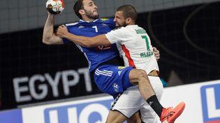 L'arrière gauche français Romain Lagarde en duel avecl'arrière gauche algérien Daoud Hichem, lors du Championnat du monde de handball masculin 2021 entrela France et l'Algérie au Caire (Egypte), le 20 janvier. (PETR DAVID JOSEK / AFP)