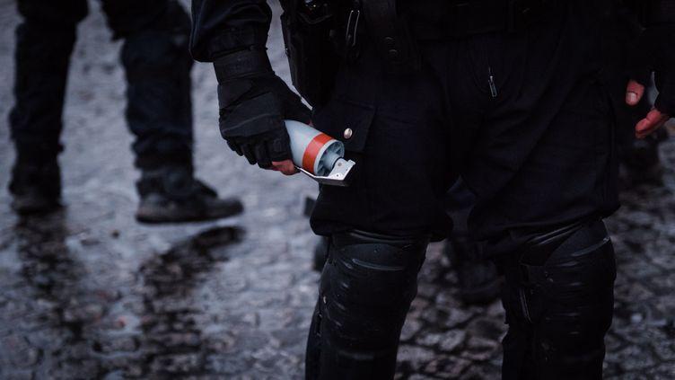 """Un policier tient à la main une grenade GLI-F4, lors d'une manifestation des """"gilets jaunes"""", sur la place de la Bastille, à Paris, le 26 janvier 2019. (KARINE PIERRE / HANS LUCAS / AFP)"""