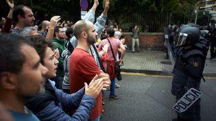 Despoliciers font face à des Catalan, dimanche 1er octobre, à Barcelone en Espagne. (ALAIN PITTON / NURPHOTO / AFP)