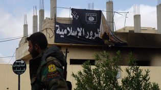 Un drapeau du groupe Etat islamique sur un immeuble dePalmyre (Syrie), le 27 mars 2016. (MAHER AL MOUNES / AFP)